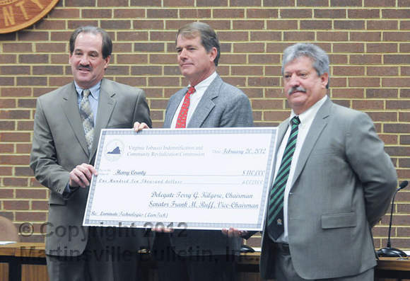 Butch Hamlet (center) of the Virginia Tobacco Indemnification and Community Revitalization Commission presents a check for $110,000 to Henry County Supervisors Chairman Jim Adams (left) to assist with the LamTech project. Fred Zoeller, LamTech president, CEO and co-founder, is at right. (Bulletin photo by Mike Wray)