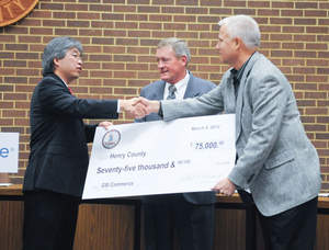Virginia Secretary of Commerce and Trade Jim Cheng (left) shakes hands with Mike Bomba, vice president of fulfillment services for GSI, as they hold a check for $75,000 in grant funds to assist with the project.